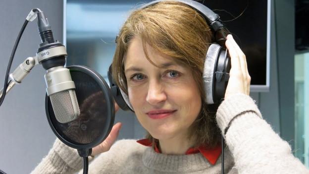 Frau mit Kopfhörern vor Radiomikrofon.