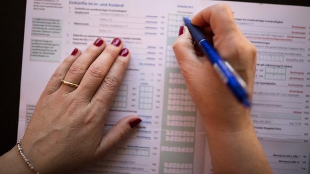 Zwei Frauenhände über einem Steuererklärungsformular.