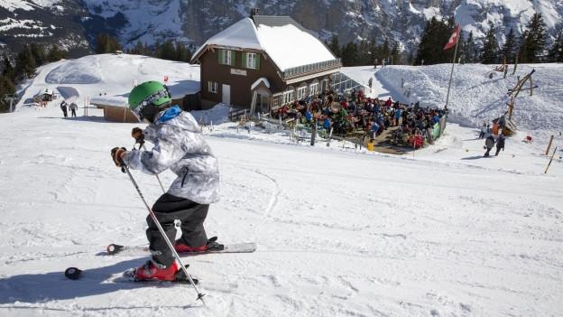 Ein Kind auf Skis vor einem Bergrestaurant.
