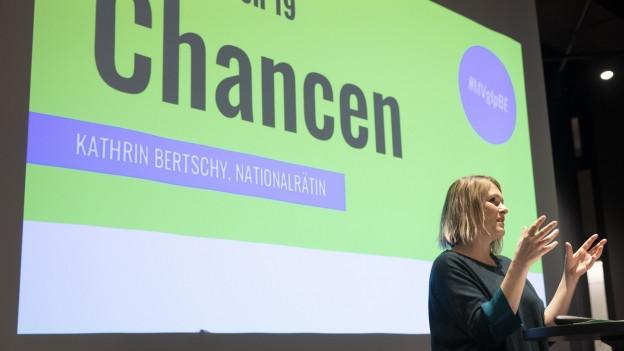 Kathrin Bertschy an Mitgliederversammlung vor Leinwand.