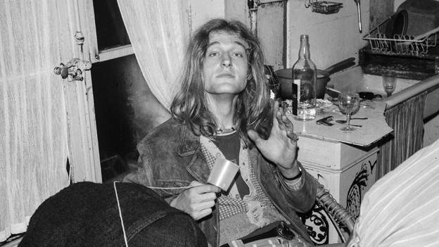 Schwarzweiss Foto: Junger Mann mit langen Haaren an einem Tisch;