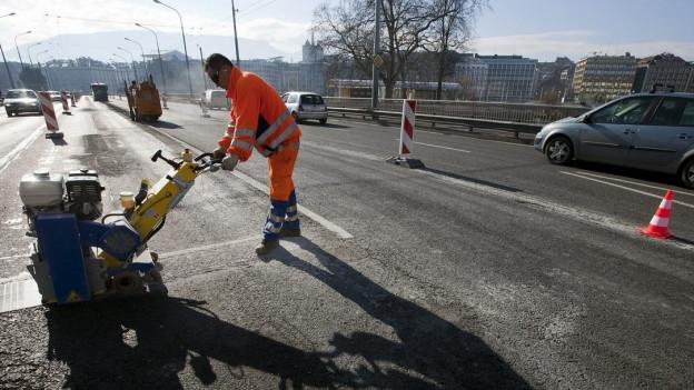 Ein Bauarbeiter arbeitet am Strassenbelag.