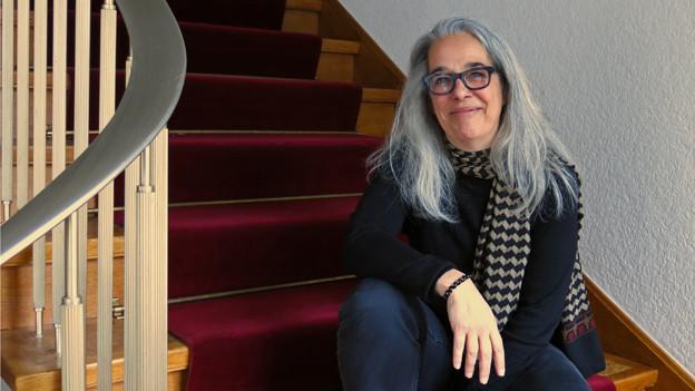 Eine Frau sitzt auf einer Treppe.