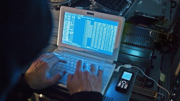 Ein Mann tippt Befehlszeilen in seinen Laptop.