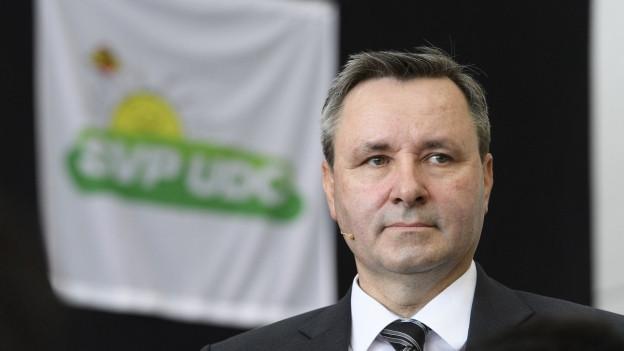 Porträt Werner Salzmann, im Hintergrund SVP-Logo
