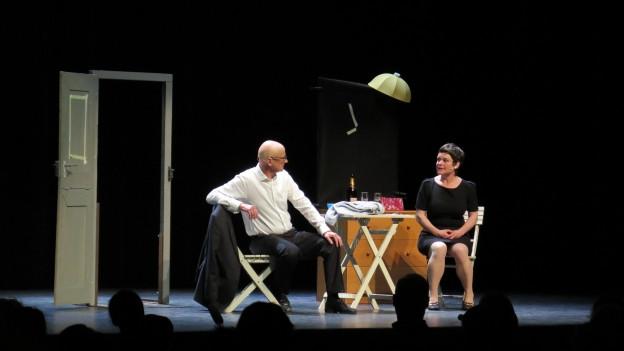 Bühne mit zwei Schauspielern, Publikum im Vordergrund (im Schatten)
