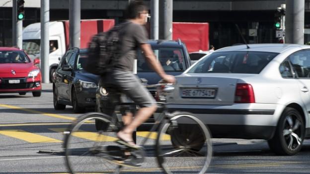 Mann auf Velo im dichten Autoverkehr.