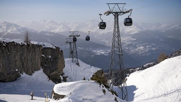 Eine Seilbahn fährt oberhalb schneebedeckter Pisten.