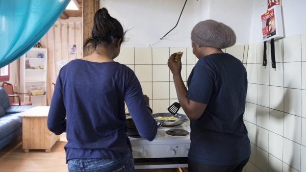 Zwei junge Frauen stehen an einem Herd und kochen.