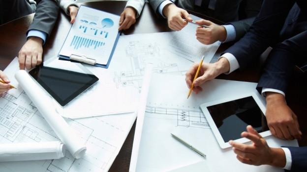 Geschäftsleute an einem Tisch mit Dokumenten und Tablets