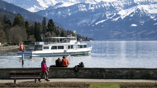 Schiff auf Thunersee, Spaziergänger im Vordergrund.