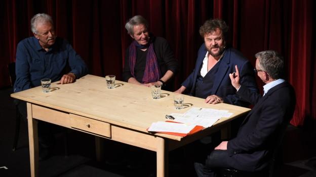 Vier Männer sitzen um einen Tisch.
