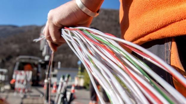 Ein Mann hält ein Bündel farbiger Kabel in der Hand.