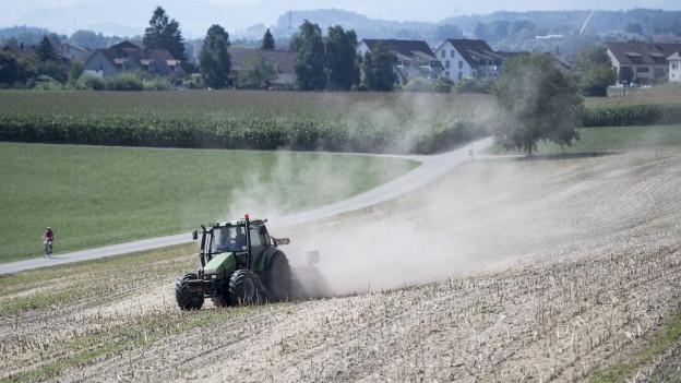 Traktor pflügt Feld und verursacht dabei eine grosse Staubwolke.