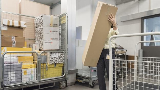 Postmitarbeiter trägt ein Paket, weitere Pakete im Hintergrund