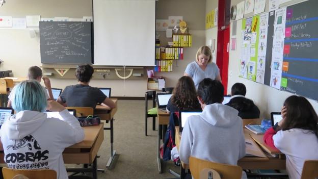 Auf dem Bild ist eine Schulklasse zu sehen, die an Laptops arbeitet