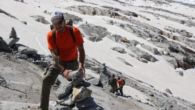 Die Zivilschützer markieren den neuen Weg mit Steinmännern.