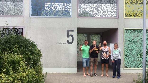 Vier Menschen stehen vor einem Haus und lachen