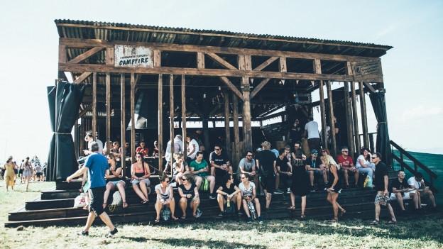Holzhütte auf Rasen, auf der Treppe vor dem Haus sitzen Leute.