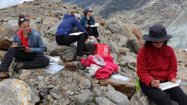 Vier junge Frauen sitzen auf Fels und zeichnen.