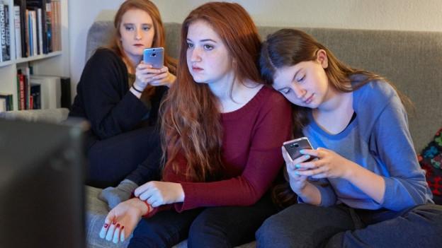 Mädchen benutzen ihre Smartphones während sie im Wohnzimmer auf dem Sofa sitzend fersehen.