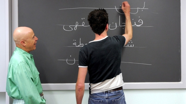 Auf dem Bild zu sehen ist ein Kursteilnehmer, der unter Aufsicht des Lehrer arabische Wörter an der Wandtafel zu schreiben übt.