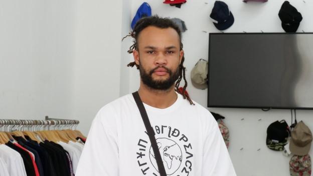 Auf dem Bild zu sehen ist Rapper Nativ der in einem Kleiderladen posiert.