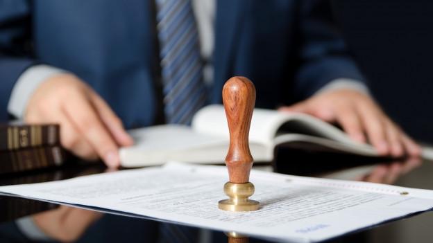Auf dem Foto ist ein Mann im Anzug zu sehen der vor Dokumenten sitzt.