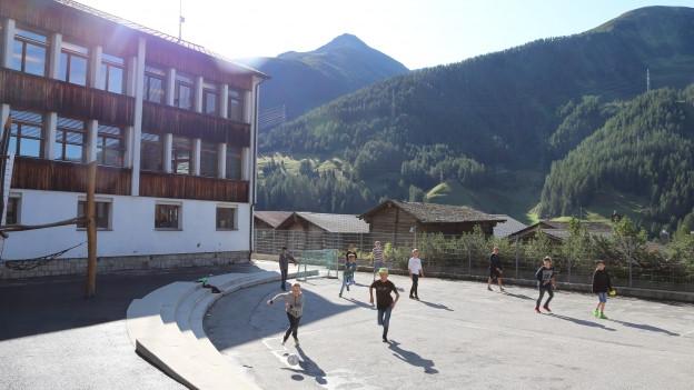 Auf dem Bild sind Kinder zu sehen die Fussball auf dem Pausenplatz spielen.