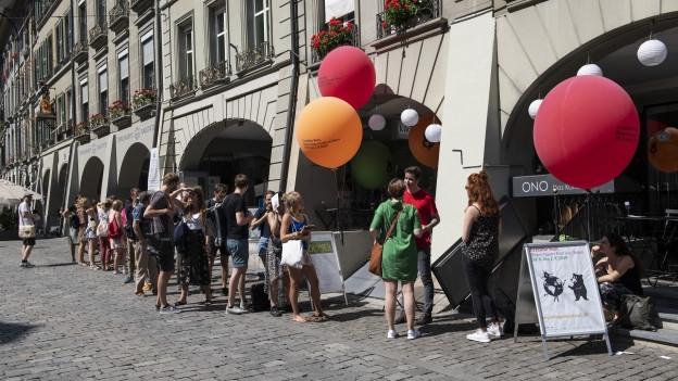 Leute stehen vor dem Kulturlokal ONO in Bern, Ballone des Festivals in der Luft