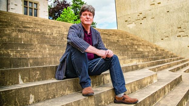 Ein Mann sitzt auf einer Treppe.