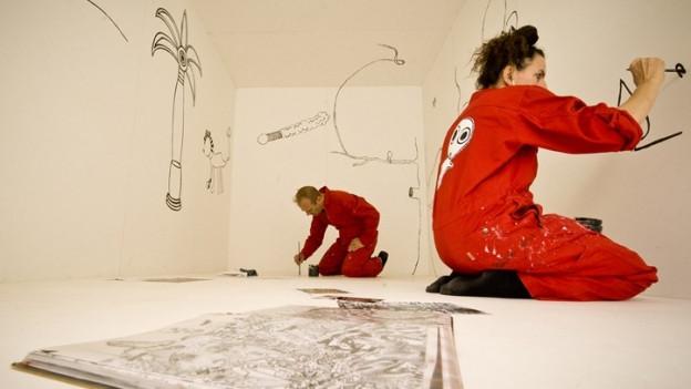 Zwei Personen in rotem Overall bemalen Wände in einem weissen Raum