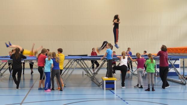 Viele Kinder in farbigen T-Shirts und Sporthosen stehen um zwei grosse Trampolins herum. Zwei von ihnen springen darauf.