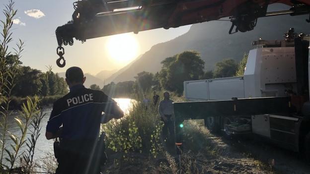 Polizisten der Kantonspolizei Wallis bergen ein Autowrack aus der Rhone bei Leytron.