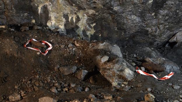 Auf Fels liegt alte Munition, markiert von weiss-rotem Plastikband.