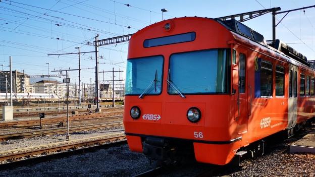 Ein oranger RBS-Zug steht in einem Bahnhof.
