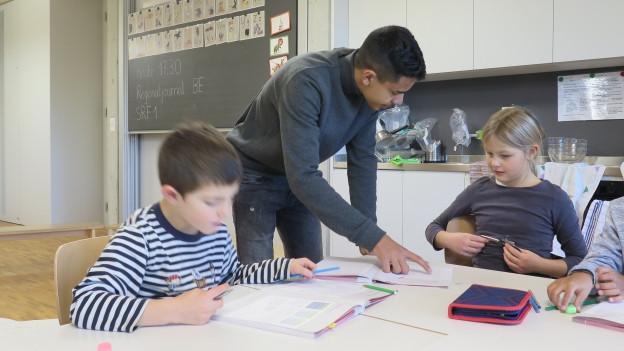 Jugendlicher steht am Tisch von jüngeren Schülern.