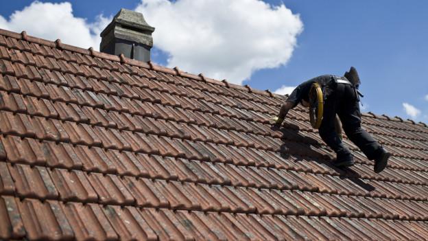 Ein Kaminfeger auf dem Dach.