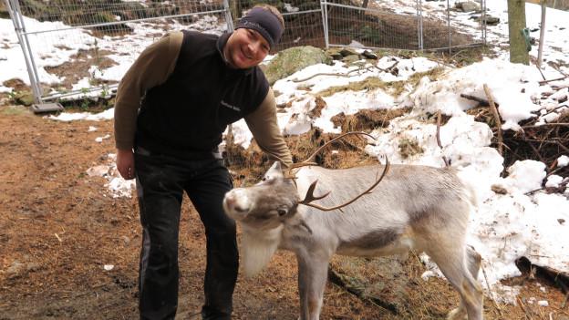 Ein Mann in warmer Kleidung lächelt in die Kamera, vor ihm steht ein graues Rentier.