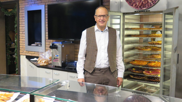 Mann mit Brille steht vor einem Regal mit Kuchen.