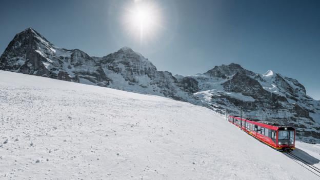 Ein roter Zug fährt vor Berggipfeln durch eine verschneite Landschaft.