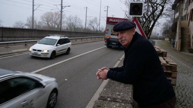Ein Mann schaut vorbeifahrenden Autos zu.