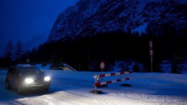 Auto vor Absperrung im Mattertal, nachts