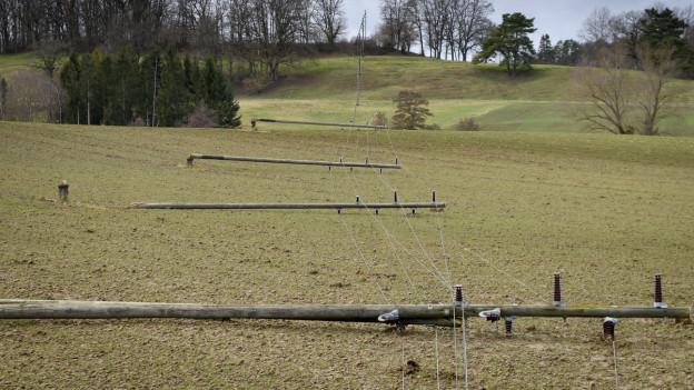 Umgeknickte Strommasten liegen auf einem Feld.