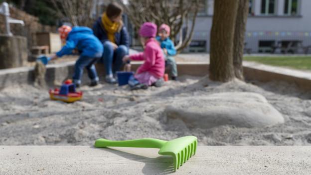 Kinder spielen im Sandkasten.