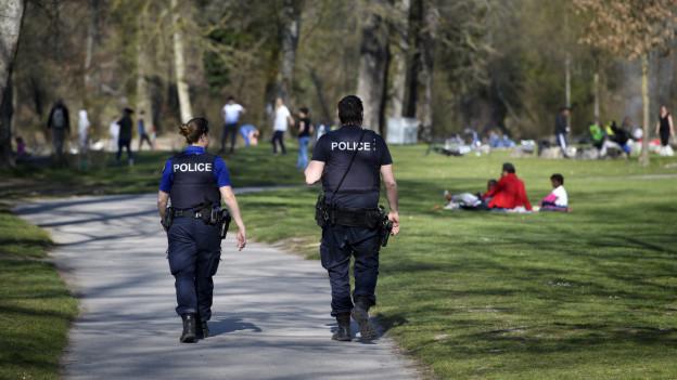 Zwei Polizisten auf Patrouille – von hinten fotografiert.