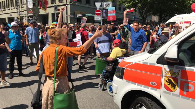 Menschen vor einem Polizeiauto