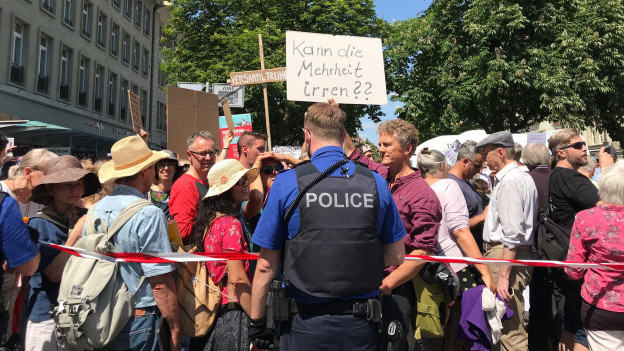 Polizist hält Demoteilnehmer auf