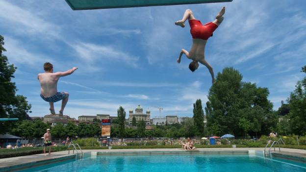 Zwei Junge Männer springen im Marzili vom Sprungbrett
