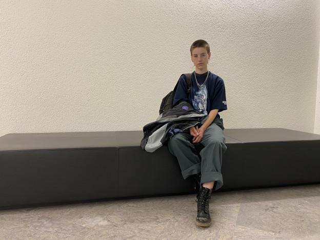 Die Autorin sitzt vor einer weissen Wand auf einem Sofa
